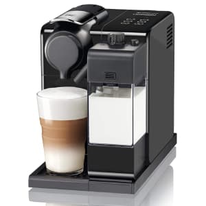 Macchina da caffè nera Nespresso Lattissima Touch Animation con bicchiere di latte macchiato e bricco per il latte pieni su sfondo bianco